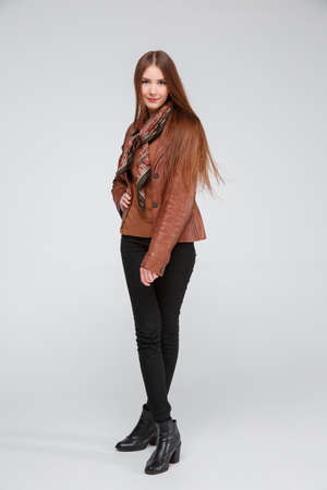 Beautiful brunette in a brown leather jacket posing cross-legged against a gray background.