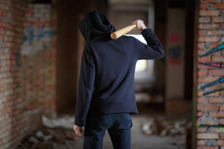 A man in a hood with a bat on his shoulder stands facing the exit on an abandoned building view from the back.