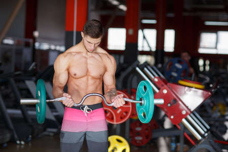A guy with a W-bar makes exercises on a blurred background of the gym
