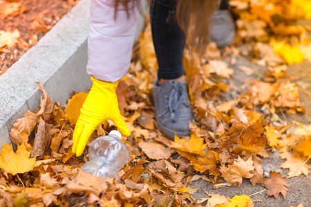 Girl raises garbage in an autumn park close up Stock Photo