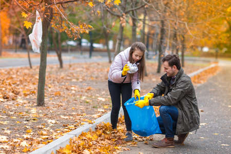 The girl throws garbage into the package that Papa keeps Stock Photo