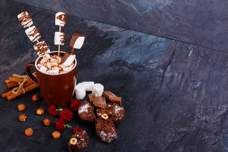 A cup of hot chocolate with marshmallows in chocolate on a stick next to hazelnuts, flowers, marshmallow and cinnamon sticks Stock Photo