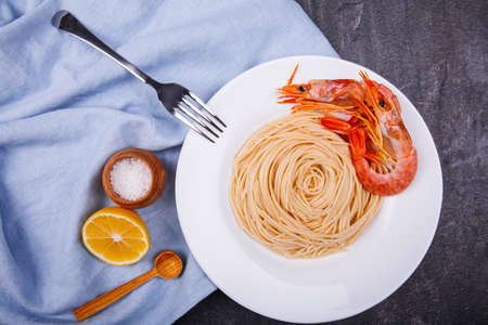 Dinner with spaghetti and king prawns and slice of lemon.
