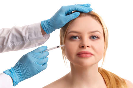 The doctors hands inject into the face woman. Isolated .