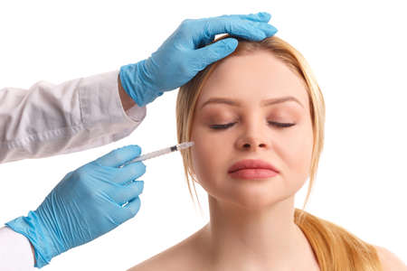 The doctor injects on the cheek of a beautiful woman.
