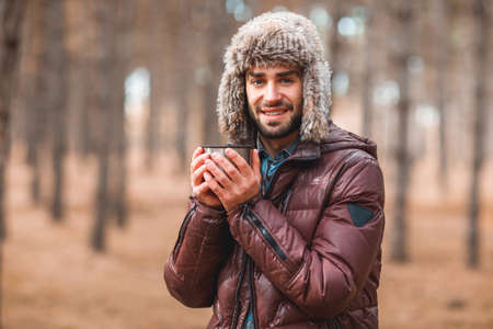 An attractive guy warms his hands holding a thermo mug. In the autumn forest.