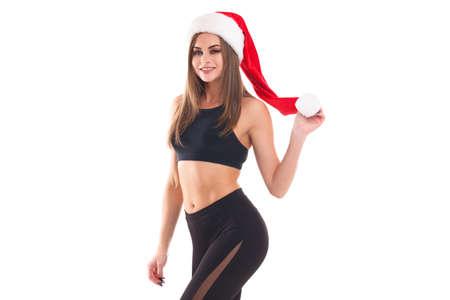 Muchacha deportiva que sostiene una bola en un sombrero de la Navidad en un fondo aislado blanco