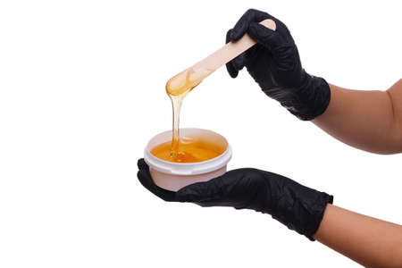 Hand holding a jar of sludge paste on a white isolated background Stock Photo