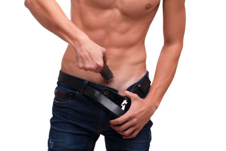 A guy shaves his hair with a trimmer underneath his belly on a white isolated background