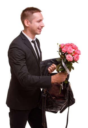The guy took out a bouquet from a bag and wants to give it on a white isolated background