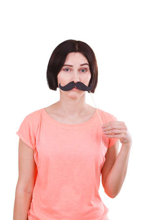 A girl posing to herself a mustache on a stick against a white isolated background