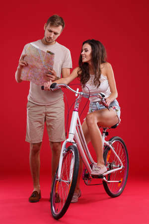A guy looks at the map and shows the girl on a bicycle on a red background