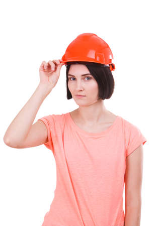 A girl is holding one hand behind a hard hat against a white isolated background Stock Photo