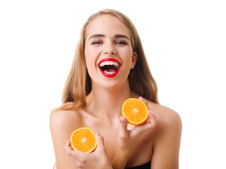A girl with a smile holds two halves of an orange in hands on a white isolated background