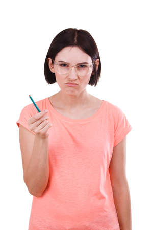 A girl angry with a pencil in her hand on a white isolated background Stock Photo
