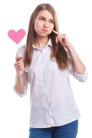 Girl with heart on stick is touching puffed cheeks on white isolated background
