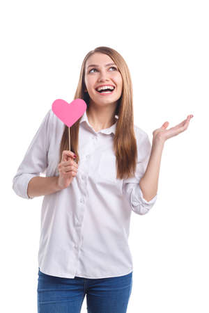 A girl with a smile and a heart on sticks waving her hands on a white isolated background