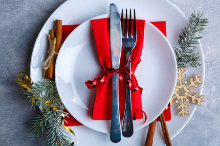 Plate in a plate with a knife and a fork tied with a ribbon on a red napkin on a stone background. Top view of a closeup Standard-Bild