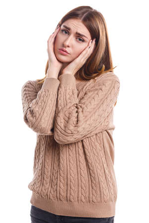 A girl is holding her hands on her side of the head on a white isolated background
