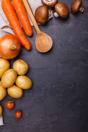 Wooden spoon with vegetables next to a towel close-up on a stone background Banco de Imagens