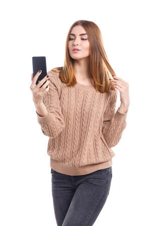 A young girl does selfie on the phone on a white isolated background