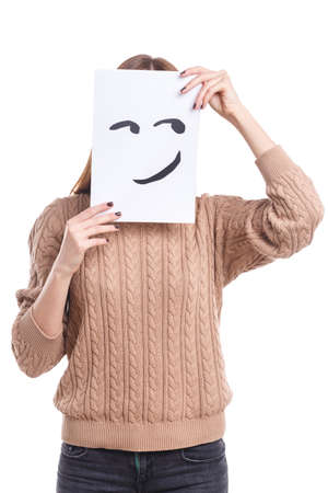 The girl covers her face with a smiley face sheet with a smirk on a white isolated background Stock fotó