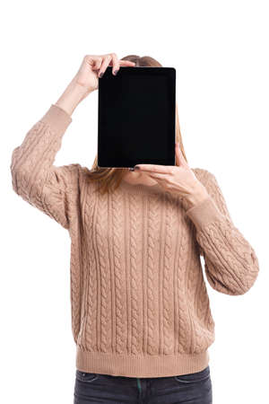 Girl covers her face with a tablet on a white isolated background