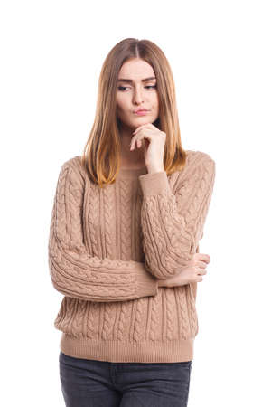 A girl is holding her hand on her chin with a pensive look on a white isolated background Stock fotó