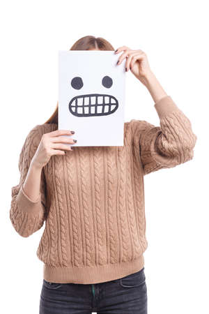 Girl covers her face with a white leaf with a sad smiley on a white isolated background Stock fotó