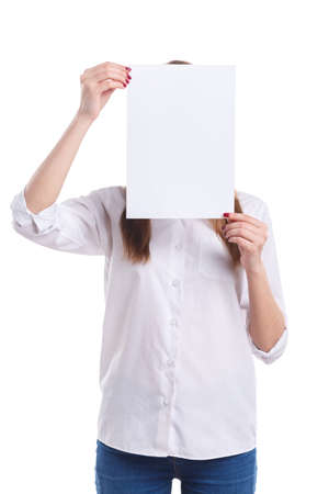The girl covers her face with a white sheet of paper on a white isolated background