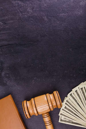 The brown notepad, the wooden hammer of the judge and a bundle of dollars lay with a fan on the bottom against a stone background. View from above Stock Photo