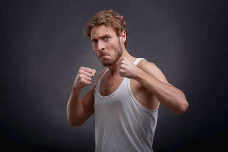 Ein Mann, der böswillig und ernst gemeint ist, steht in der Kampfhaltung und ist halb auf einem schwarzen Hintergrund abgebildet