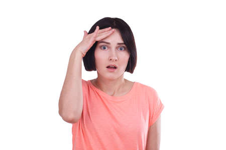 A girl with a fear in her eyes put her hand to her forehead on a white isolated background Stock Photo