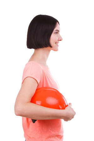 The girl is holding a helmet in her hand. Side view on white isolated background Stock fotó