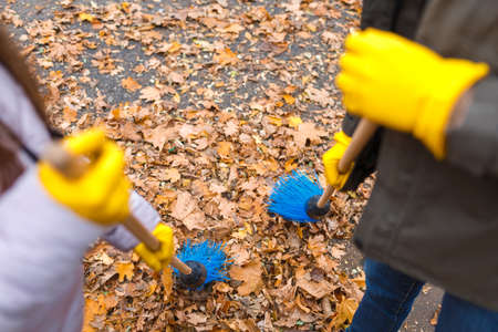 Dad and daughter in yellow prints sweep blue broom leaves on the road in the autumn park