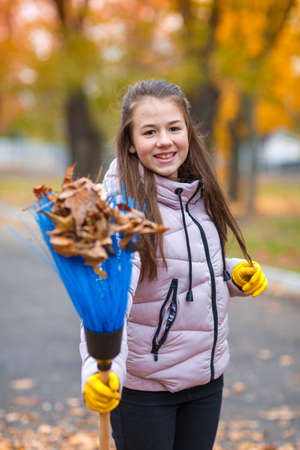 The girl is holding a broom in which the leaves are stuck on the blurred background of the autumn park