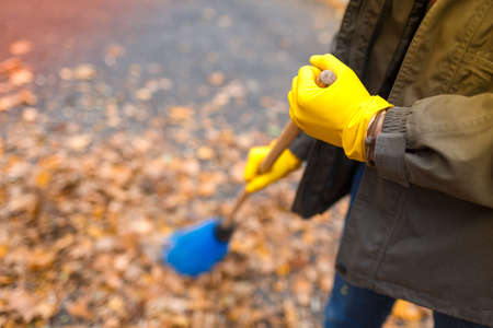 Hands of the father in yellow gloves in focus with a broom against the background of fallen leaves on. Autumn park.