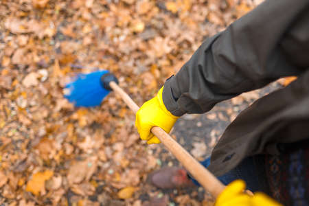 His fathers hands sweep the leaves in the park Stock Photo