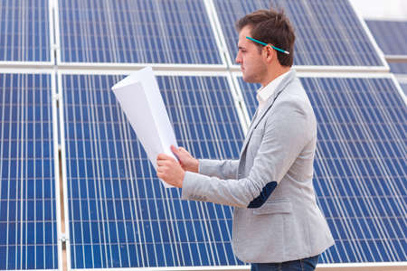 The chief looks at the project in his hands against the background of solar panels