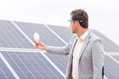 The boss holds a light bulb in his hand and look at it against the background of solar panels
