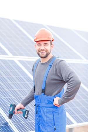 Worker with a screwdriver in his hand on a background of solar panels