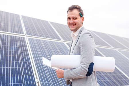 The chief is holding a notebook and the project is folded under his arm against the background of solar panels Stock Photo