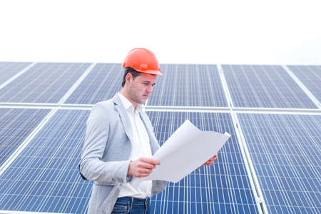 The chief stands sideways looking at the project in hand against the background of solar panels