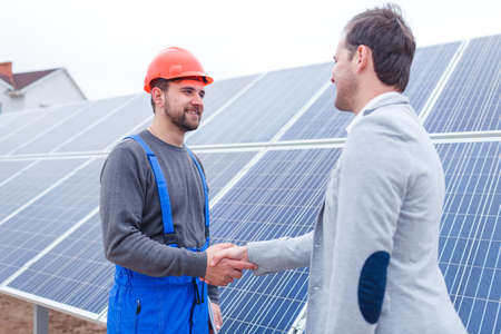 The chief shakes hands with the worker against the background of solar panels