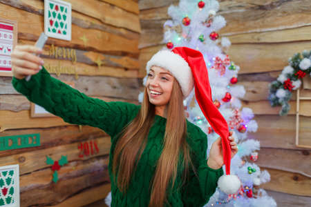 A young girl in a santa hat makes selfie on the background of a Christmas tree