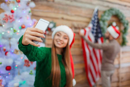 A young girl in a santa hat makes a selfie on the background of a man who hangs an American flag on the wall. Stock Photo
