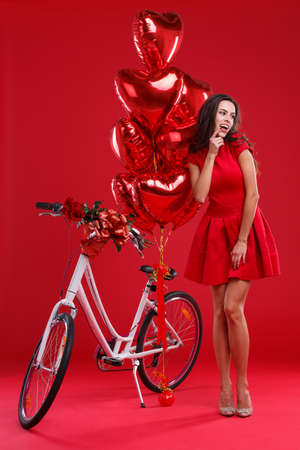 A young girl in a red dress, received a bicycle with big red balls as a gift, looks away.