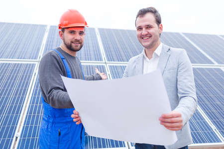 The chief keeps the Whatman next to the worker on the background of solar panels
