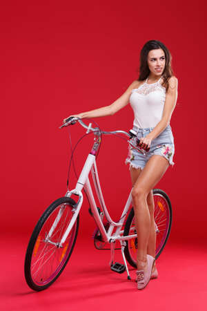 Young girl posing on red background standing near bicycle. Stock Photo