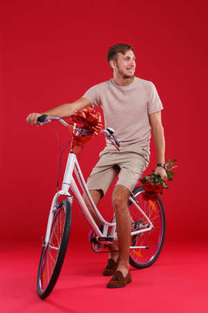 A young guy sitting on a bicycle who wants to give, with flowers in his hands. Stock Photo